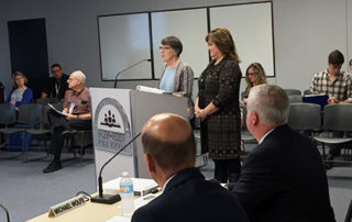 People talking at podium during board meeting