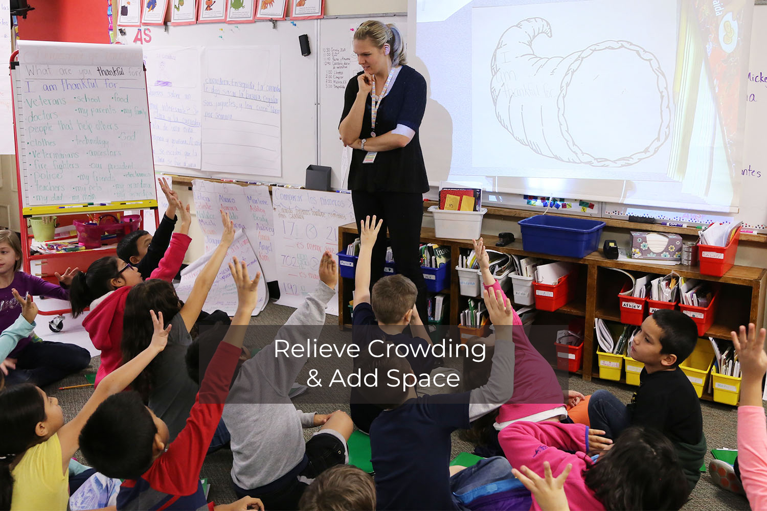 Female teacher in front of elementary students who are sitting on the floor and raising their hands